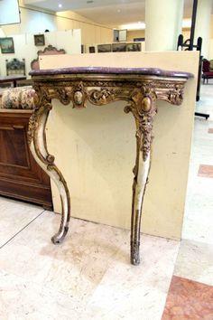 Epoca: Seconda metà dell'Ottocento  Consolle in legno laccato e dorato con piano in porfido. 79 x 34 h 91 cm.