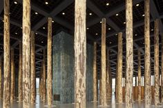 Using 144 imposing tree trunks, British architect David Chipperfield transforms the open glass hall of the Neue Nationalgalerie into a densely filled hall of columns for a three-month period.