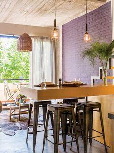 Dúplex con living comedor integrado a la cocina. En la barra, banquetas Tolix (Bruta Deco), lámparas Flor (Estación Ortiz) y vajilla Flat sobre individuales de ratán (Petite Margot).