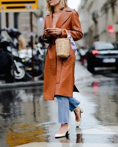 Leather trench coat styled with a straw bucket bag