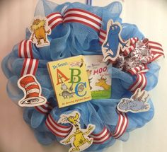 Deco mesh wreath with a dr. Seuss theme. Two mini booklettes in the center (tied in instead of glued) and various Seuss creature cut-outs. Broad red & white ribbon to accent the cat-in-the-hat storyline and look closely at the bow to see the CITH print on the secondary ribbon.