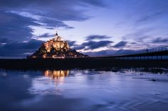 Mont Saint Michael with water reflection during night time