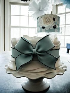 Anne Kathleen cakes. Fondant ruffles and tied with a large fondant ribbon cake , and a polka dot cake with a huge fondant flower.
