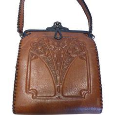1920's Arts & Crafts Embossed Leather Purse Handbag by Nocona Bags. An incredibly beautiful Nocona leather purse embossed in a distinct Arts and Crafts or Art Deco era design. The bag dates to the early 1920's era. It is made of supple honey brown leather. The embossed design on the bag's front depicts a graceful lily of the valley motif.  The single strap handle and edges on the bag body are laced in a dark chocolate leather whip stitch. The sides of the bag were hand sewn by artisans as wa...