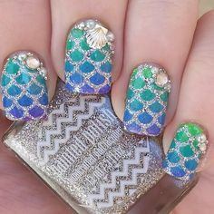 Dazzling silver holographic scales with plush pearls, gold clam and caviars adorn this cool blue green gradient base. DIY this fanciful mermaid-inspired nail art with these how-tos and products here.