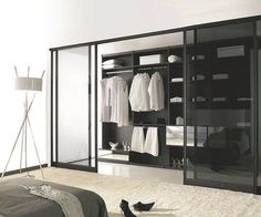 Derrière de théâtrales portes coulissantes en aluminium et verre fumé noir, un dressing réalisé sur mesure par Coulidoor.
