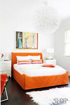 White bedroom with orange bed frame and patterned pillows.