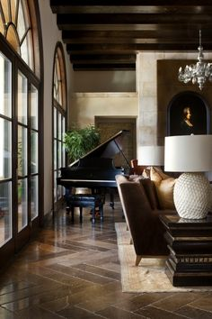 dreamy living room with dark wood beams across the ceiling & a baby grand piano.