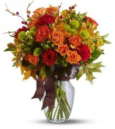 A mix of fresh flowers such as roses, chrusanthemums, carnations and alstroemeria--in shades of orange, green, yellow and red, and with accents such as hypericum, galax leaves and preserved oak leaves--is delivered in a clear glass vase adorned with a brown stain ribbon. #ChantillyFloralBoutique #FallForColor