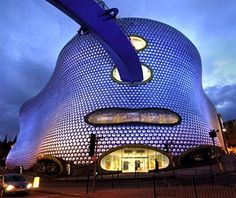 """The Birmingham branch of Selfridges is a billowy mattress of a building, clad in 15,000 shimmery aluminum discs like that famous Paco Rabanne dress. It was designed by Future Systems- the name tells you pretty ;much everything you need to know about the firm-to be a landmark and a catalyst for the revitalization of a largely moribund city center. """"An ersatz urban cliff, a giant sea anemone, a friendly, blob-like alien, the mother of all magic mushrooms,"""" wrote Guardian architecture critic…"""