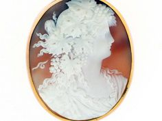 This extremely fine antique Victorian intricately carved shell cameo is designed with a neoclassical female silhouette with Bacchante details of grape clusters, grape leaves, and the head of a lion.
