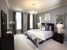Mirrors behind the night stands. Grey walls and curtains with dark bed and tables