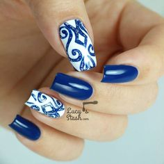 Beautiful blue dark blue nail art design inspired by lace designs. The lace-like designs are painted in blue glitter polish against a white background while the rest of the nails don an electric blue shade.