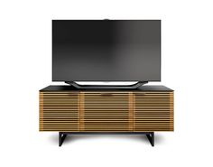 The CORRIDOR 8177 TV cabinet is three compartments wide. The center drawer pulls out to reveal a full-width soundbar speaker shelf and a media storage drawer.  Finish: White Oak