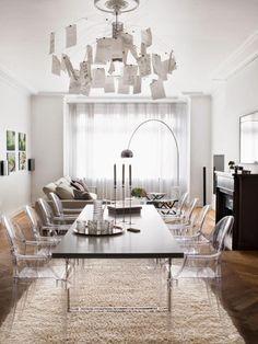 salon et salle à manger 2 en 1 aménagés avec des chaises médaillon transparentes, table à manger noire et tapis shaggy blanc