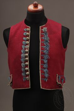 Mužská vesta z tmavě vínově červeného sukna, zdobená našitý polokulovitými stříbrnými litými gombíky s motivem květu. Na obou přednicích všita kapsa. Zdobená modrými prýmky a třepením. Na okrajích je lemována prýmkem režné barvy. Na zadním díle pod prostředním švem je nastřižený šůsek, pod postranními švy jsou čtyři hustě složené záhyby, prošité tak, aby stály a v pase jsou ukončeny modrým třepením. Šířka: 48,5 cm x 2, Délka: 47,4 cm. 1870 až 1879. Národní muzeum. Inventární číslo: H4-5460