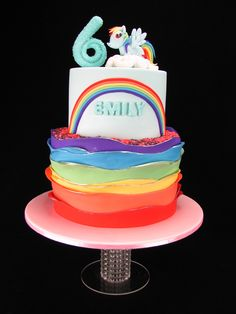 A fondant Rainbow Dash Pony on top of a rainbow cake. There's a lot of rainbows here, inside and out. The top tier is a dummy cake but the bottom tier is a rainbow layer vanilla cake with Smarties waiting to spill out of the centre. The edges of the rainbow waves are painted silver for sparkle and there are Nerds on top.