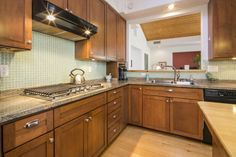 Craftsman Kitchen with Kitchen island, Complex Granite, L-shaped, Hampton Bay Shaker Cognac Cabinets, Flat panel cabinets