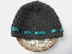This dark gray hat features a dark teal ribbon decal. It is the perfect hat to keep your babys head toasty warm. This hat makes a great shower gift and the colors are gender neutral, making it perfect for the mom who doesnt know the gender of her new baby. This hat fits babys 2-4 months old, but since crochet is naturally stretchy, it may fit for even longer.  This item was made in a cat friendly non smoking home.  This item is machine washable and dryer friendly.  If you like this hat, but…