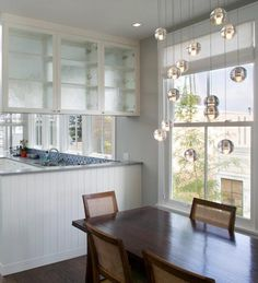 a bocci glass light fixture over the dining table catches and reflects daylight breakfast table lighting