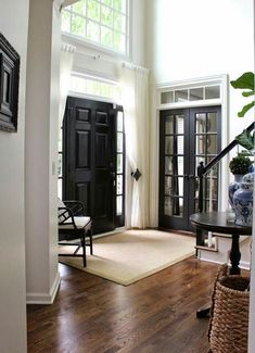 Entryway with black doors and curtains to close windows.