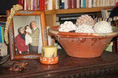 Moldura com aplicações de estanho; grinalda de flores; porta-vela (vela em taça de barro tradicional); alguidar de barro tradicional com bolas forradas de conchas