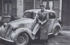 Michael Wittmann poses next to a small staff car, pin by Paolo Marzioli