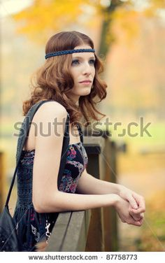 Beautiful hippie girl thinking on a wooden bridge in autumn scenery wearing maxi long dress and gorgeous make up. by cellistka, via ShutterStock