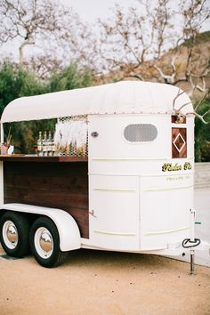 Rustic wedding inspiration! Let our Tinker Tin bar trailers like this 1948 horse trailer bar transform your barn or rustic wedding! The 1948 Trail King horse trailer bar has reclaimed wood siding, wrap around bar, and 2 built in tap handles! It is perfect for serving craft cocktails or beer at any wedding or event!- Tinker Tin vintage trailer rentals