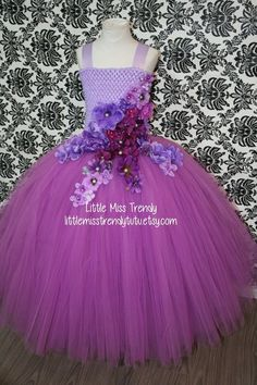 This dress is like no other! Its dainty and so sophisticated and elegant at the same time. This dress is made up of orchid purple tulle with a lined lilac crochet top. An assortment of purple, lavender, lilac and bluish purple flowers are in an intricate design on the front of this dress (theres no flowers on the back), going down into the skirt. Straps are in lilac satin ribbon and tie beautifully into a bow in the back. There are 4 layers of tulle on this dress. This Tutu Dress is perfect…