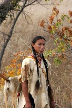 A Native American Indian man in the prairie of South Dakota plains indians sioux indian relationship with the land earth warrior weapon hunt hunting scout scouting battle war search searching portrait pose teenager boy