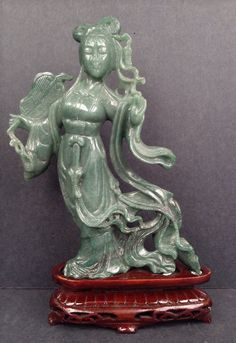 """A JADE CARVING FIGURE OF A BEAUTY - Jade carving of Beauty with smooth lines and curves and elegant pose; standing on elaborate decorative carved mahogany fitted wood base. 10""""H x 7""""L x 2.5""""W (id-510468)"""