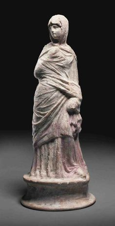A GREEK TERRACOTTA FIGURE OF A WOMAN HELLENISTIC PERIOD, CIRCA 3RD CENTURY B.C. Standing with weight on right leg, wearing long chiton and closely wrapped himation which covers her head as a veil, standing on integral circular plinth, rectangular vent hole at the back, remains of pink pigment over white slip 8¾ in. (22.2 cm.) high, Christie's.
