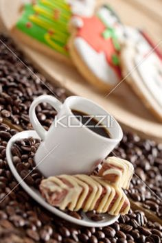 image of coffee cup with beans and cookies. - Close-up tilt image of black coffee cup with chips cookies and coffee beans with gingerbread candy in background.