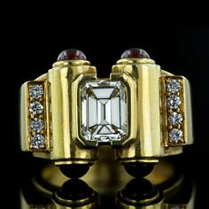 18K yellow gold, scroll-motif estate ring centered with a 1.65 carat emerald-cut diamond, accented with four cab rubies and eight round diamonds, $ 8,950 (Image: Lang Antiques)
