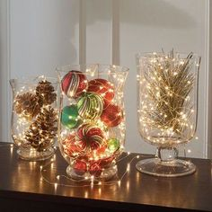 Easy Christmas table top decoration idea using vases. Simply get a an empty vase, add your desired object & complete the look with a battery operated fairy string lights. These battery operated Christmas lights are very portable and comes in different color. Since these are battery operated, you can easily hide its battery compact and get this Christmas holiday decoration