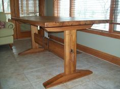 Here's a red elm version of our somewhat shaker style trestle table. It has iron adornments on the stretcher and the pegged ends.