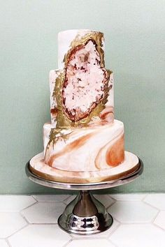 Peach and pink swirls wrap this rose-quartz-colored geode wedding cake, giving it movement.