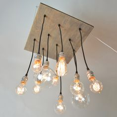 """ made from reclaimed wood with a gray stain, silver hardware and varying vintage-style Edison bulbs. Each design features 10 bulbs and can be mounted flush against the ceiling or suspended"" I think I can have hubby whip up one similar to this for our game room!"