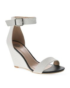 Opt for a versatile shoe with these SnakeskinWedge Sandals by Footwork. These minimal, wedge-heeled sandals are white in colour, feature a slim front-foot strap and a silver-tone buckled ankle strap. Displaying synthetic uppers and a durable sole, these sandals are rounded off by a snakeskin finish. Pair them with distressed boyfriend jeans, a white vest and a plaid shirt for a cool, grunge look.