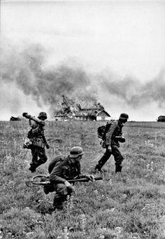 German soldiers from division Grossdeutschland. The first on the left is carryng what seems to be an anti-tank rocket launcher, the one in the middle is equipped with a portable flame -thrower that he could have used to set the house in the background on fire.Date and location unknown, but most likely Russia.