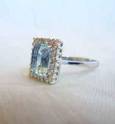 A Natural Emerald Cut Aquamarine and Diamond Halo Engagement