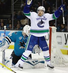 Vancouver Canucks' Daniel Sedin, right, celebrates after scoring a goal against San Jose Sharks goalie James Reimer (34) during the second period of an NHL hockey game Saturday, March 5, 2016, in San Jose, Calif.