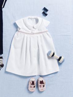 Ganz in Weiß empfangen kleine Mädchen ihre Taufe. süße Details sind der Bubikragen, mit Batist gedoppelte Miniärmelchen und dekoratives Ripsband in der erhöhten Taille.