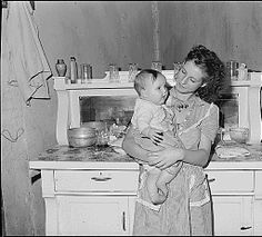 Mrs. Lincoln Hagg with her baby in the kitchen of her house. Panther Red Ash Coal Corporation, Douglas Mine, Panther, McDowell County, West Virginia., 08/26/1946