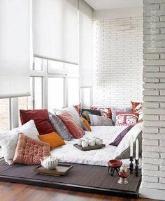 Une espace très hygge avec une surabondance de coussins et un grand matelas sur fond de brique peinte