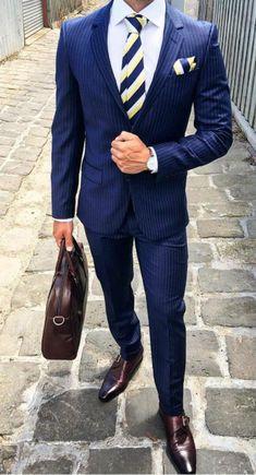 homme d'affaires, costard bleu avec cravate aux rayures diagonales en bleu roi et blanc, chaussures en couleur bordeaux et porte-sac élégant en couleur bordeaux