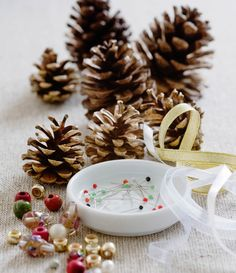 - Making pine cone decorations with beads - STEP 2. All the equipment needed: pine cones, beads, pins and ribbons. -  -