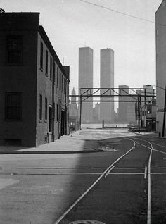 "n-architektur: ""Light and shadow with railroad tracks and century brick warehouse against the World Trade Center looming across the Hudson.March 1975 Photo via Andy Blair "" World Trade Center Nyc, Trade Centre, Jersey City, Sacramento, 11 September 2001, Vintage New York, City That Never Sleeps, Tours, Light And Shadow"