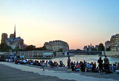 セーヌ川に吹く夕暮れの風を楽しんでいるパリジェンヌやパリジャンたち。